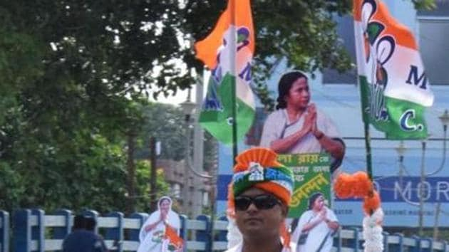 A TMC supporter rides a scooty with a cut-out of West Bengal Chief Minister Mamta Banerjee and party flag on it in Kolkata on Thursday.(ANI Photo)