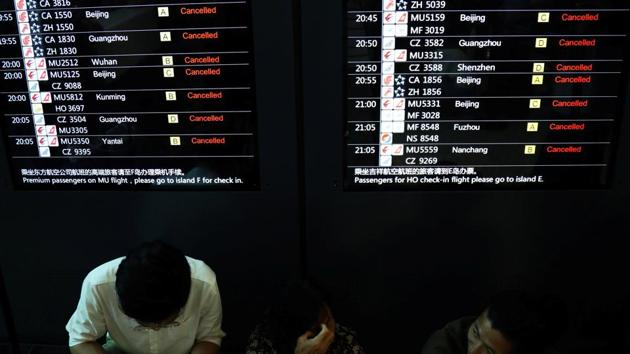 People sit before an information screen showing flights cancelled in anticipation of Typhoon Lekima at the Shanghai Hongqiao International Airport. More heavy rain was forecast for the Shanghai area and the neighbouring provinces of Anhui, Jiangsu and Zhejiang, with authorities warning of possible flash floods, mudslides and landslides caused by the downpours. (Tang Yanjun / CNS via REUTERS)