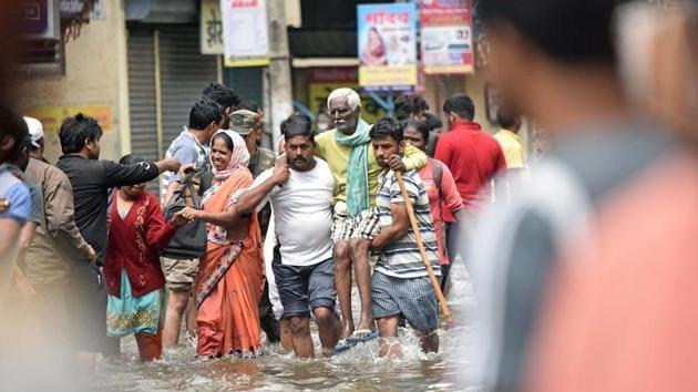 People walk through flooded Streets of Sangli.(Pratham Gokhale/HT Photo)