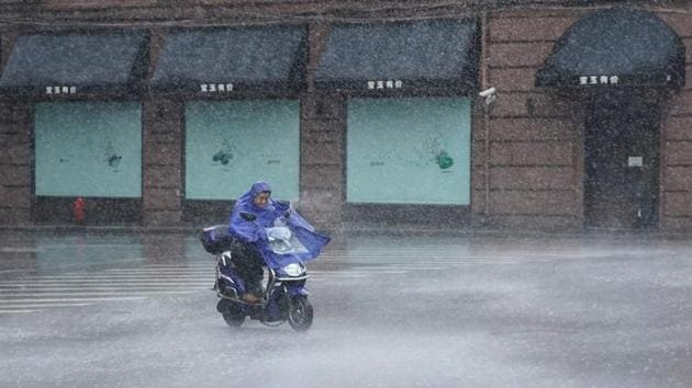A man rides an electric scooter in the rainstorm as typhoon Lekima approaches in Shanghai. The monster storm made landfall in the early hours in Wenling City, packing winds of 187 kilometres per hour (116 miles per hour), and was expected to churn up the east coast towards Shanghai, Xinhua added. (Aly Song / REUTERS)
