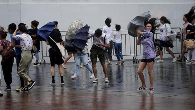 People walk in the rainstorm as Typhoon Lekima approaches in Shanghai. Waves several metres high hit the coastline as the storm made landfall in Zhejiang province, south of Shanghai. (Aly Song / REUTERS)