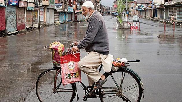 A Kashmiri man rides a bicycle through a deserted street during security lockdown in Srinagar. (Photo PTI)