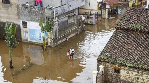 A man walks through a flooded area following incessant rainfall in Maharashtra's Kolhapur district.(PTI)