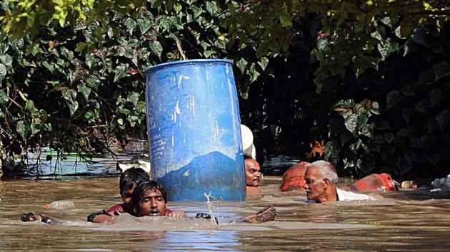 Villagers wade through the flooded street after heavy rainfall at Krishna Lanka in Vijayawada, Andhra Pradesh(ANI Photo)