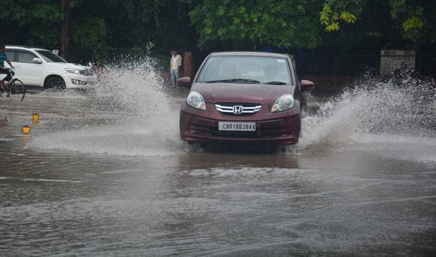 Vehicles negotiate a waterlogged roundabout in Sector 10, Panchkula, on Saturday.(Sant Arora/HT)