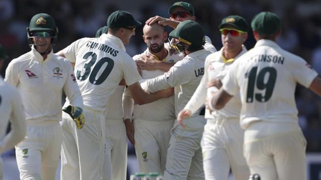 Australian players congratulate Nathan Lyon, centre, after dismissing England's captain Joe Root.(AP)