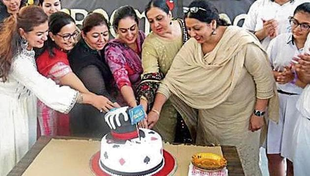 Student and teachers cutting a cake.