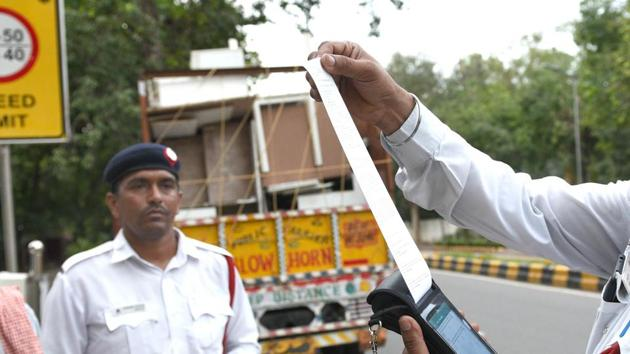 Delhi Traffic Police personnel issue a fine to a truck driver after the implementation of the amended Motor Vehicles Act that came into force today, near KG Marg in New Delhi, India, on Sunday, September 1, 2019. A man angered over a huge challan set his bike on fire on 5th September, 2019.(Arvind Yadav/HT PHOTO)