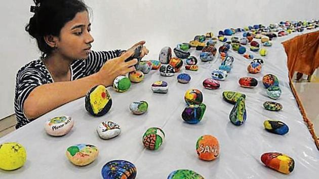 Stone paintings with awareness messages painted on them were given out as gifts at the exhibition.(praful gangurde/HT)