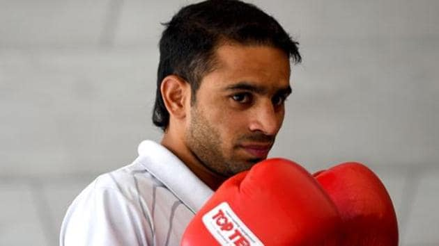 Indian boxer Amit Panghal poses for photographs wearing his gloves.(AFP)