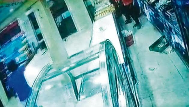 The helmet-clad man (left) pointed the pistol at the staff (right) behind the delivery counter and shot four rounds.(cctv camera grab)