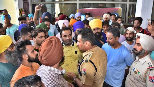 A cop trying to pacify protesters in Ludhiana on Tuesday.(HT Photo)