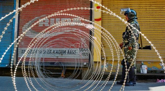 A security person stands guard at a blocked road during restrictions, after the abrogration of Article of 370 and bifurcation of state, in Srinagar, Monday, Sept. 9, 2019.(PTI file photo)