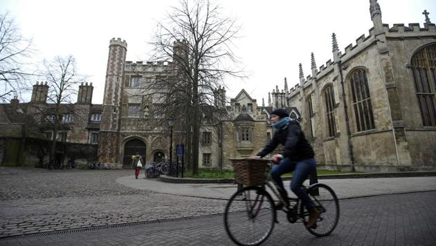 A cyclist rides a bicycle past Trinity College, part of the University of Cambridge, in Cambridge, U.K.(Bloomberg Photo)