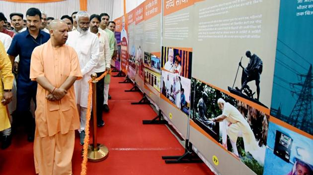 Uttar Pradesh Chief Minister Yogi Adityanath in the exhibition showcasing the work done by Prime Minister Narendra Modi, at BJP Headquarters in Lucknow .(ANI Photo)