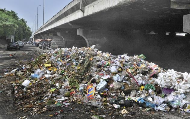A heap of garbage under the flyover near the bus stand in Ludhiana on Wednesday.(HT PHOTO)