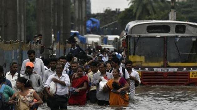 People walk through a flooded street following heavy monsoon rains at LBS road Kurla, Mumbai, September 4, 2019(Kunal Patil/HT Photo)