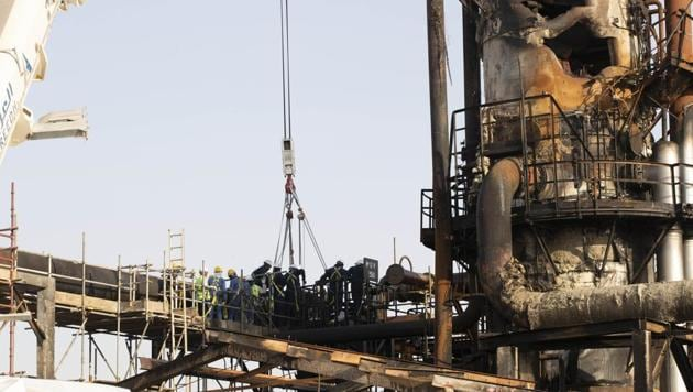 Workers repair a damaged refining tower at Saudi Aramco's Abqaiq crude oil processing plant following a drone attack in Abqaiq, Saudi Arabia, on Friday.(Bloomberg Photo)