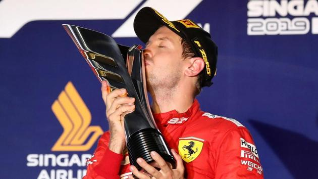 Ferrari's Sebastian Vettel kisses the trophy as he celebrates after winning the race.(REUTERS)