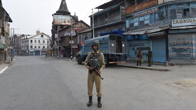 A paramilitary soldier stands guard on an empty road during restrictions, at Lal Chowk, in Srinagar, Jammu and Kashmir.(HT Photo)