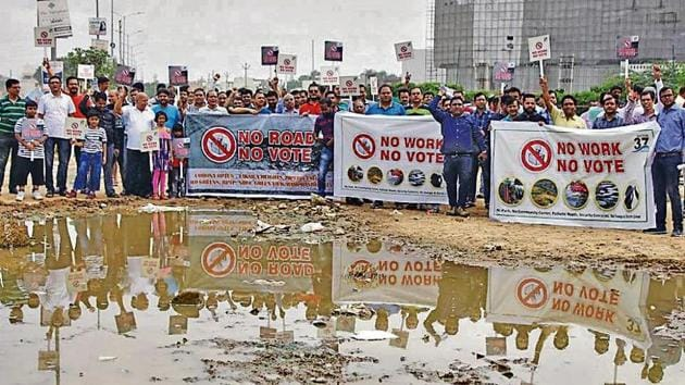 Residents of sector 37C and 37D of Gurugram during the 'no road, no vote' campaign to protest against the lack of roads, infrastructure, water drains in the area, in Gurugram.(HT Photo)
