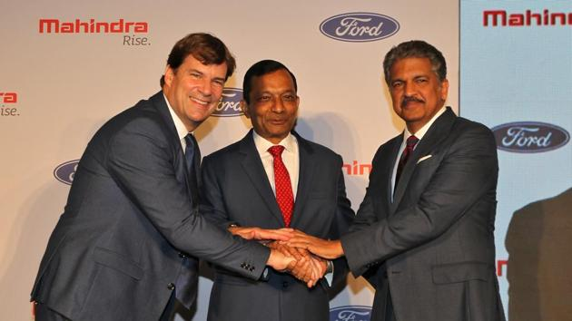 Jim Farley, President of Ford New Businesses, Technology & Strategy, Pawan Goenka, Managing Director of Mahindra & Mahindra Limited, and Anand Mahindra, Chairman of Mahindra Group, join their hands after attending a news conference in Mumbai.