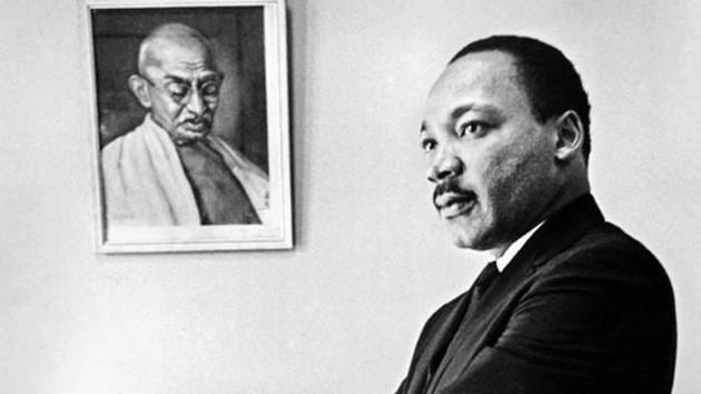 Dr Martin Luther King, Jr stands next to a portrait of Mahatma Gandhi in his office in 1966.(Bob Fitch Photography Archive, Department of Special Collections, Stanford University Libraries)
