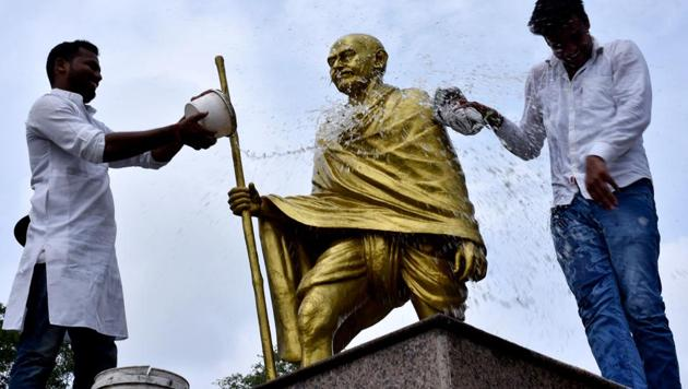 Congress Youth workers clean statue ofMahatma Gandhi on the eve of his 150th birth anniversary, in Prayagraj on Tuesday.(ANI)