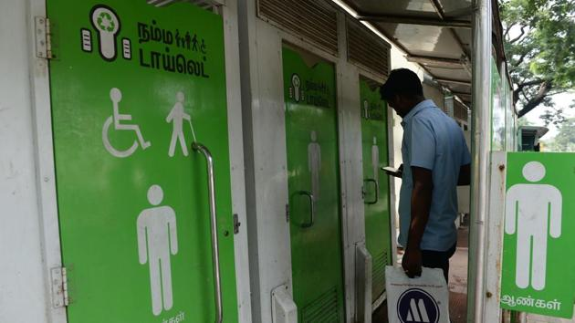A resident checks his phone as he waits to use a public toilet on a street in Chennai, Tamil Nadu. Many of the toilets that have been constructed are not being used and it is not unusual for them to be locked, used for storage, or some other purpose. (Arun Sankar / AFP)