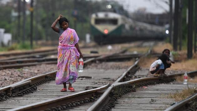 A woman walks on train tracks near young girls squatting in an area where people defecate in the open near Nizamuddin railway station in New Delhi, on September 27, 2019. Prime Minister Narendra Modi declared rural India open-defecation free (ODF) on the 150th birth anniversary of Mahatma Gandhi yesterday. Experts, however, are of the view that millions still lack access to a toilet and many of the new facilities are unused. (Prakash Singh / AFP)