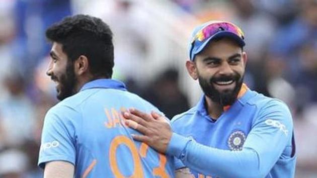 India's captain Virat Kohli, right, celebrates with teammate Jasprit Bumrah(AP)