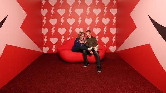 """A couple poses for a photo during a visit to the Instagram museum """"Smile Safari"""". (REUTERS)"""