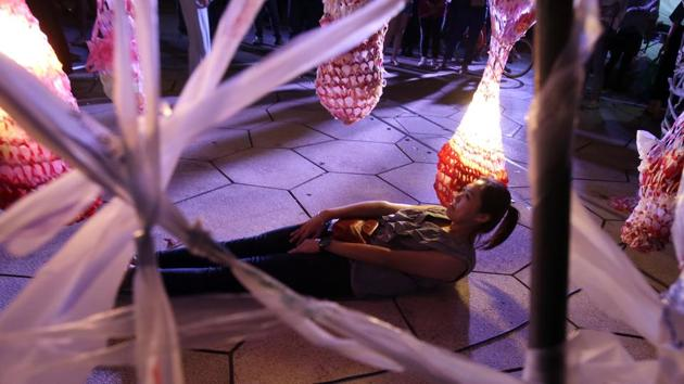 A woman lies underneath the work of Taiwanese artists Peng yu-hong and Yang Fang-Yi titled 'Weaving the Plastic Souls, at the Nuit Blanche Taipei 2019 in Taipei. (AP)