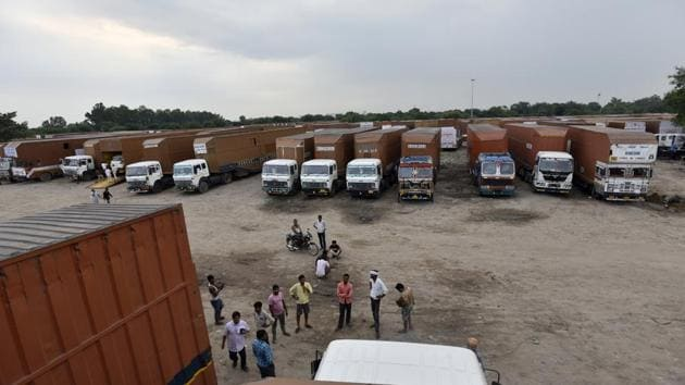 Trailer truck drivers wait their turn at a parking yard where they bid time after a slowdown in the auto sector.