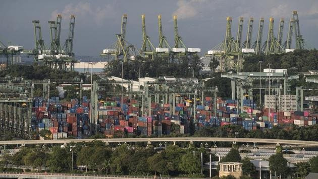 Stacked containers sit among gantry cranes at the Port of Singapore in Singapore in July 12, 2019. In its latest assessment of the factors behind productivity and long-term economic growth, the organization best-known for its annual gathering of the elites in the Swiss ski resort of Davos found Singapore overtaking the United States as the most competitive country.(Representative Image/Bloomberg File Photo)