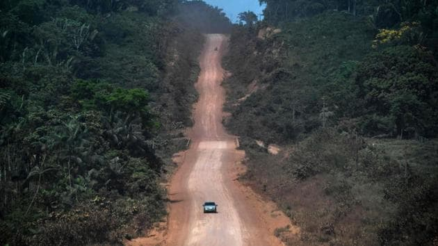 A car drives along a section under construction of the Trans-Amazonian highway (BR230) near Ruropolis, Para state, Brazil, in the Amazon rainforest. The BR230 and BR163 are major transport routes in Brazil that have played a key role in the development and destruction of the world's largest rainforest, now being ravaged by fires. (Nelson Almeida / AFP)