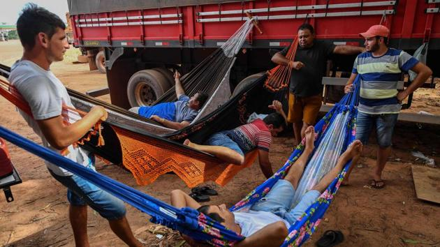 "Trucker Erik Fransuer (L) rests on hammocks with others at a gas station. Fransuer spends months driving back and forth on highways that cut through the Amazon delivering soy or corn to river ports. ""I like the freedom of being on the road,"" Fransuer said. He spends at least 12 hours a day sitting in his big rig listening to fast-paced music as he bounces along the highways constructed nearly 50 years ago and somehow still not finished. (Nelson Almeida / AFP)"