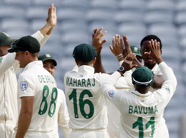 South Africa's Kagiso Rabada, right, celebrates with teammates the dismissal of India's Rohit Sharma during the second cricket test match between India and South Africa in Pune. (AP)