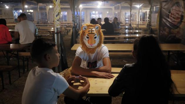 Children, one wearing a tiger mask, sit at a table in the food area of an autumn fair in Titu, southern Romania. Thousands flock to fields outside small cities, where entertainment areas are set up from mid-week until the weekend. (Vadim Ghirda / AP)