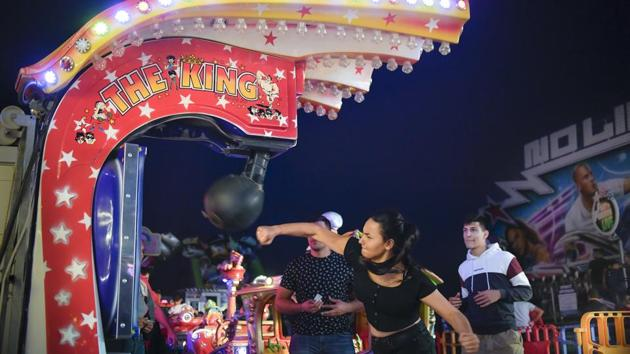 A girl hits a boxing power punch machine at the fair. Music and flashing lights strike visitors on arrival at the fairground, which is constantly engulfed in smoke from the food grills and an endless mix of food flavours. (Andreea Alexandru / AP)