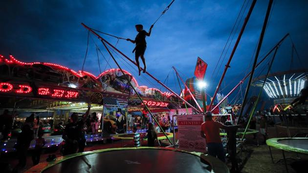 A child jumps on a trampoline at the fair. While younger people focus on the fairground rides and games, the elderly take advantage of the markets, stocking up on winter supplies of fruits, vegetables and other household items available at lower prices than in Romania's mainstream shops. (Vadim Ghirda / AP)