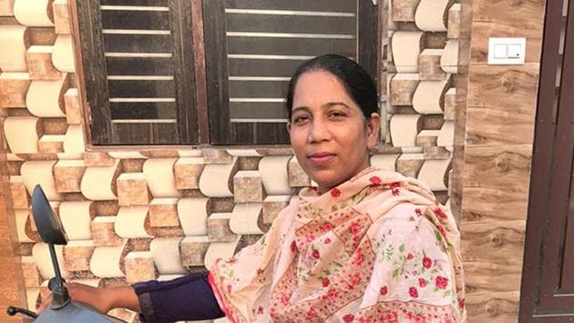 Ludhiana's first woman bike-taxi driver poses with her two-wheeler in Ludhiana on Tuesday. She took the job as it was regular and was the pathway to her independence.(HT Photo)