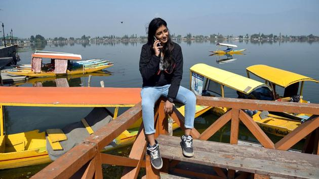 A tourist talking on her mobile phone as the Postpaid mobile services have been restored by Government, at the banks of Dal Lake in Srinagar on Monday. (ANI Photo)(ANI)