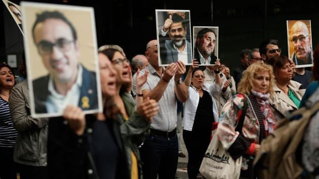 People hold placards depicting pictures of jailed Catalan separatist leaders. The longest prison term - 13 years - was imposed on the Catalan government's former deputy leader, Oriol Junqueras. The court convicted him and eight other leaders on charges of sedition and four of them of misuse of public funds. Three others were found guilty of disobedience and not sentenced to prison. All defendants were acquitted of the gravest charge, rebellion. (Pau Barrena / AFP)