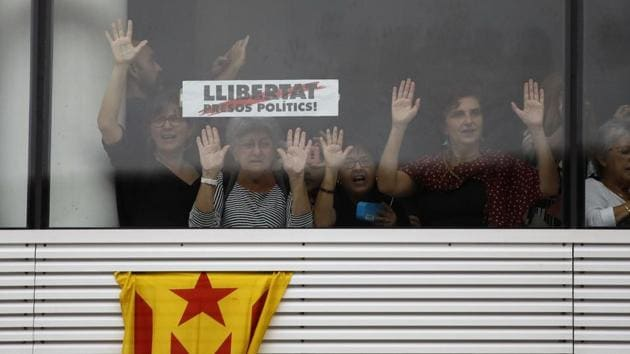 """Protesters stand behind a banner reading in Catalan, """"Freedom for Political Prisoners"""" at El Prat airport in Barcelona. Spain's Supreme Court on Monday jailed nine Catalan separatist leaders for between nine and 13 years for their role in a failed independence bid, a decision that triggered mass protests in the region and left the future course of the dispute uncertain. (Emilio Morenatti / AP)"""