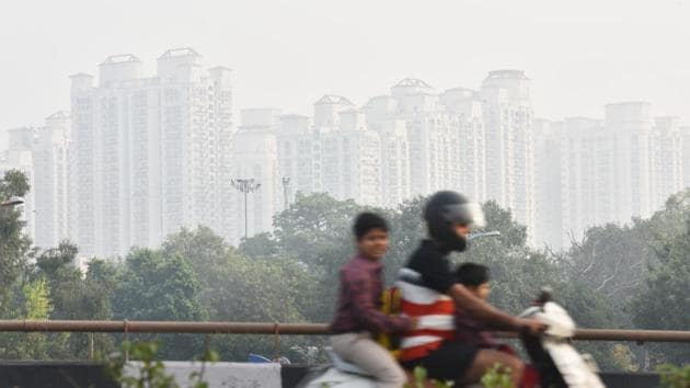 A motorist passes high rise buildings shrouded in heavy smog at Moti Nagar in New Delhi on Wednesday. System for Air Quality and Weather Forecasting and Research (SAFAR) — the ministry of earth sciences' weather and air quality monitoring system —showed that only 5% of the PM 2.5 levels recorded in Delhi came from stubble burning emissions on Wednesday. (Sanchit Khanna / HT Photo)