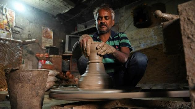 """""""I am teaching them the same way I learnt from my father, he learnt from his father and so on,"""" Kumar said as he sat at a wheel with many fresh clay pots behind him. """"People come to us from across India and not just Delhi,"""" he added. (Money Sharma / AFP)"""