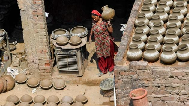 A woman carries an earthen pot inside her residence, with others in various stages of completion arranged all over. One of Jagmohan's brothers carves designs on them, then the women of the family take the finished works to the roof, where they are left to dry under the sun. Once dry, they are placed in a rooftop wood oven to bake. (Money Sharma / AFP)