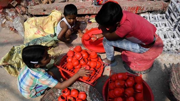 Children colour earthen pots along a roadside, at Kumhar Gram. The finished products are loaded onto rickshaws dotted around the congested pathways to be taken to nearby markets and other buyers. (Money Sharma / AFP)
