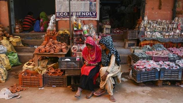 """Women use a mobile phone as they sit outside their shop displaying items made of clay, at Kumhar Gram. At a market in the village, Sushil Panwar and his wife Pratibha were buying decorations for the festivals. """"I have been coming here for a decade now. We take all clay decoration items for our home, like flower pots and earthen lamps from here,"""" Panwar said. (Money Sharma / AFP)"""